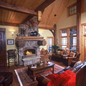 Warm, inviting hearth room features soaring wood ceilings, antique trusses, custom distressed floors and doors, stone fireplace, loads of windows, open floor plan to dining and kitchen!